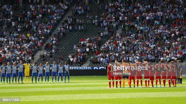Players and match officials observe a minute's silence in memory of the victims of Thursday's terrorist attacks in Spain during the Bundesliga match...