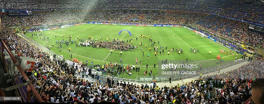 Players and officials gather on the pitch after Real Madrid won the UEFA Champions League final football match against Atletico Madrid at the San Siro Stadium in Milan on May 28, 2016. Real Madrid beat city rivals Atletico for the second time in three years to win the Champions League for the 11th time. / AFP / GIUSEPPE