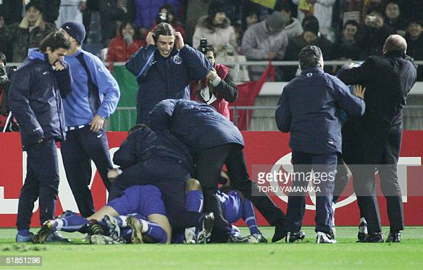Players and team staff of Portugese club FC Porto celebrate their victory on the pitch when they defeat Colombian club Once Caldas by penalty...