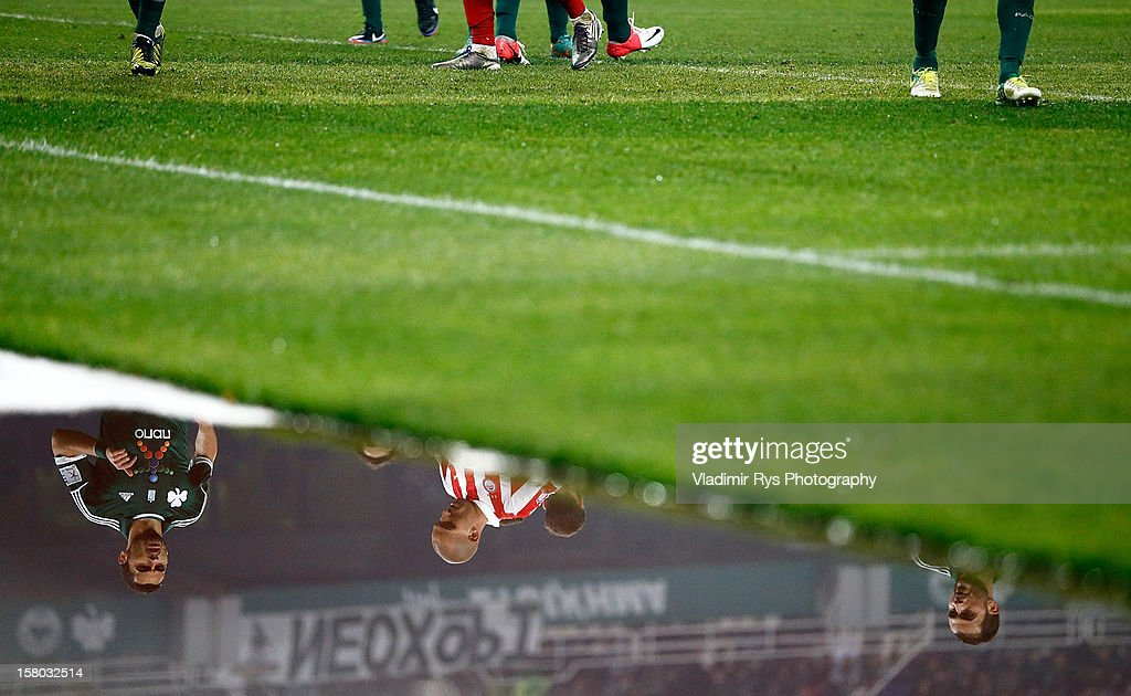 Players are pictured reflected in a water surface aside of the pitch during the Superleague match between Panathinaikos FC and Olympiacos Piraeus at OAKA Stadium on December 9, 2012 in Athens, Greece.
