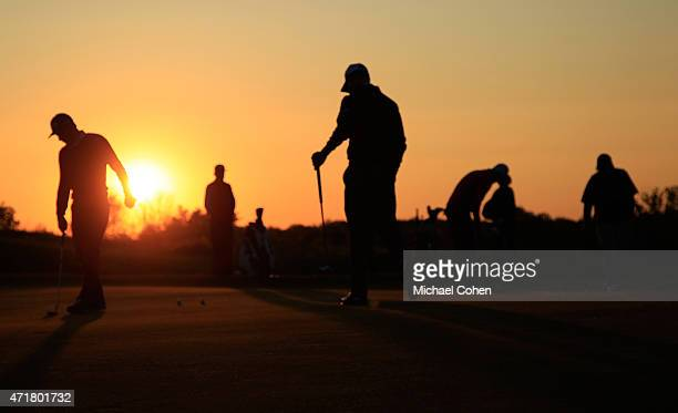 Players are seen on the putting green at sunrise prior to the start of the second round of the United Leasing Championship held at Victoria National...