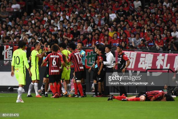 Players argue after Tomoaki Makino of Urawa Red Diamonds challenged Ken Tokura of Consadole Sapporo during the JLeague J1 match between Consadole...