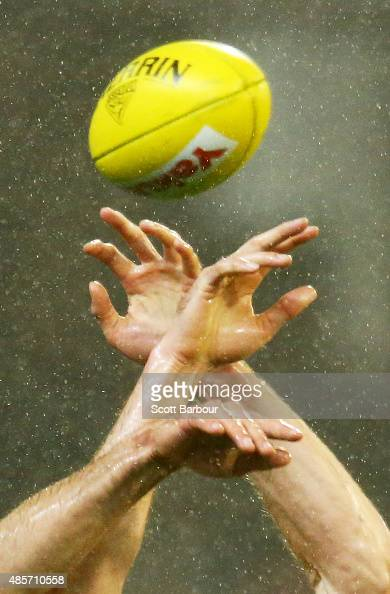 Players competes for the ball in the rain during the round 22 AFL match between the Essendon Bombers and the Richmond Tigers at Melbourne Cricket...
