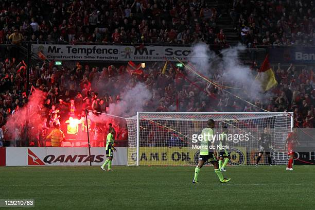 Players continue with the game after Adelaide supporters set off a flare to celebrate a goal during the round two ALeague match between Adelaide...