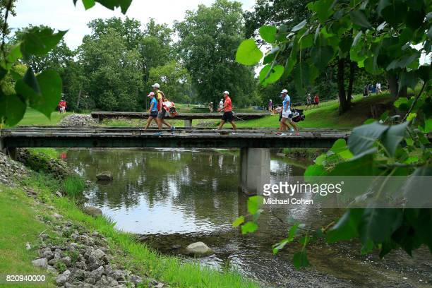Players cross the bridge to the second green during the third round of the Marathon Classic Presented By Owens Corning And OI held at Highland...