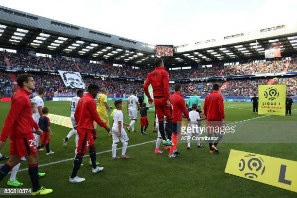 Players enter the pitch prior to the French L1 football match between Caen and SaintEtienne on August 12 at the Michel d'Ornano stadium in Caen...