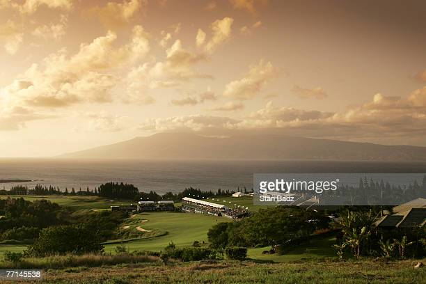 Players finish their third round at the 18th hole as the sun sets over the island of Molokai at the Mercedes Championships January 7 held at The...