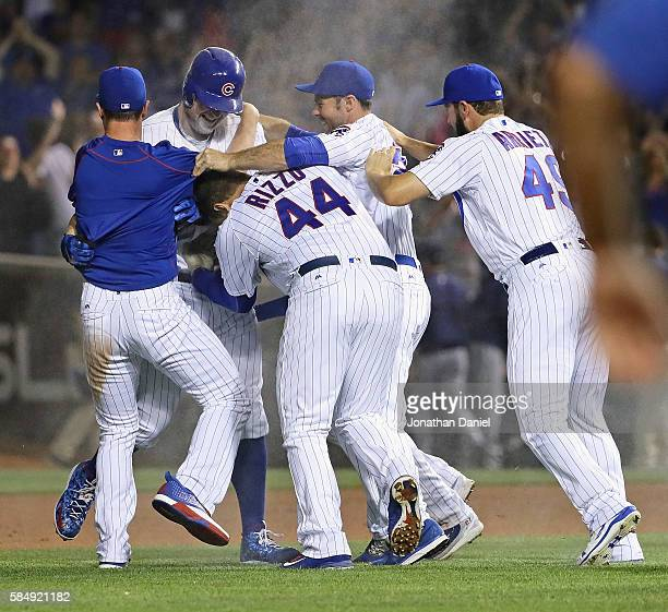 Players for the Chicago Cubs including Anthony Rizzo and Jake Arrieta mob Jon Lester after he bunted in the winning run against the Seattle Mariners...