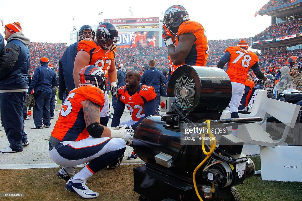 Players for the Denver Broncos stand around a heated on the sideline next to the bench against the Baltimore Ravens during the AFC Divisional Playoff Game at Sports Authority Field at Mile High on January 12, 2013 in Denver, Colorado.