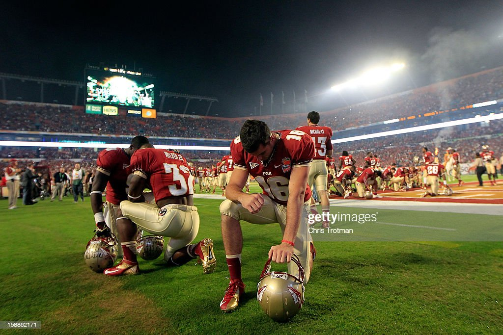 Players for the Florida State Seminoles pray on the field prior to playing against the Northern Illinois Huskies during the Discover Orange Bowl at Sun Life Stadium on January 1, 2013 in Miami Gardens, Florida.