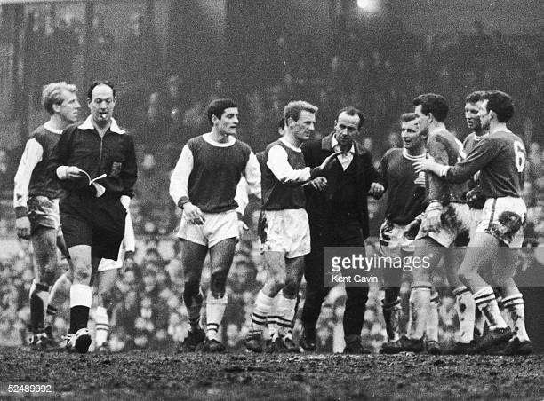 Players from both Arsenal and Leicester try to calm the situation as a spectator tries to attack the referee after Leicester were awarded a penalty...