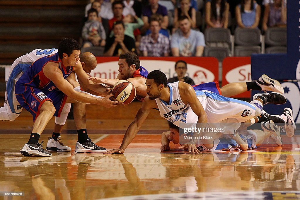 Players from both sides dive on a loose ball during the round 12 NBL match between the Adelaide 36ers and the New Zealand Breakers at Adelaide Arena on December 28, 2012 in Adelaide, Australia.