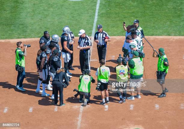 Players from both teams meet at midfield for the coin toss prior to the regular season game between the Oakland Raiders and the New York Jets on...