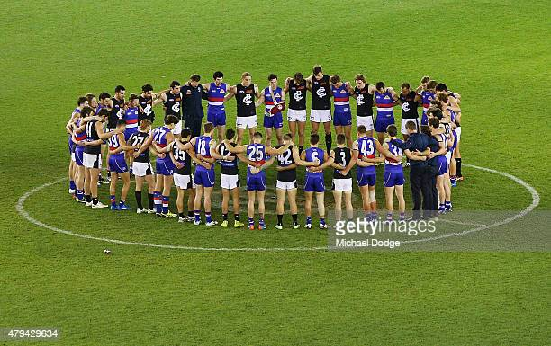 Players from both teams stand in silence around the centre circle in respect for former Adelaide Crows coach Phil Walsh who died earlier in the week...