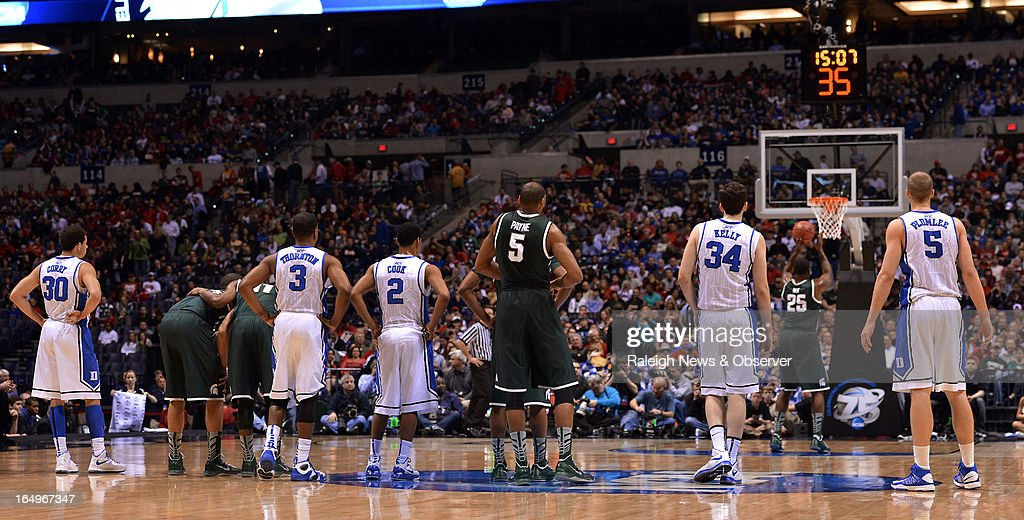 Players from both teams watch as Michigan State forward Derrick Nix (25) shoots a technical foul free throw in the first half of an NCAA Men's Basketball Tournament Midwest Regional semifinal at Lucas Oil Stadium in Indianapolis, Indiana, Friday, March 29, 2013.