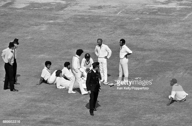 Players from England and West Indies accompanied by policemen wait on the pitch during the bomb scare on the Saturday of the 3rd Test match between...