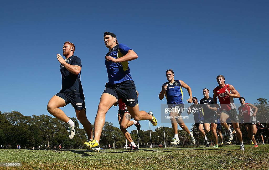 Players from English Super League club Warrington Wolves and Sydney Swans train together during a Sydney Swans AFL pre-season training session at Lakeside Oval on January 15, 2014 in Sydney, Australia.