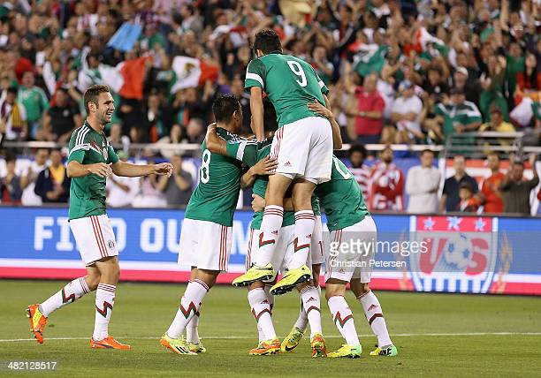 Players from Mexico celebrate around Alan Pulido after he scored a second half goal against USA during the International Friendly at University of...
