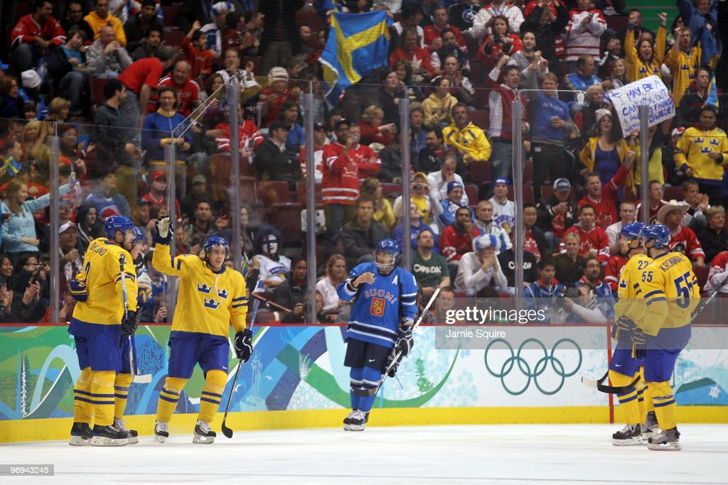 Players from Sweden celebrate after goal in the second period by Nicklas Backstrom against Finland during the ice hockey men's preliminary game on...