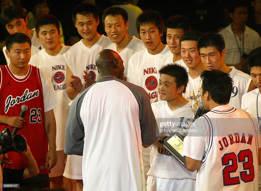 Players from the championship winning Shenyang #31 High School meet US basketball legend Michael Jordan, presenting the trophy to China's high school champions, 20 May 2004, at the Worker's Stadium Gymnasium in Beijing. Despite being a no show at open public events in the Chinese capital yesterday, Jordan's slick promotional tour has grabbed more headlines than the return to China of the nation's homegrown NBA hero Yao Ming. Shenyang's #31 High School defeated Shanghai's Nanyang Model High School for the title. AFP PHOTO/Frederic J. BROWN