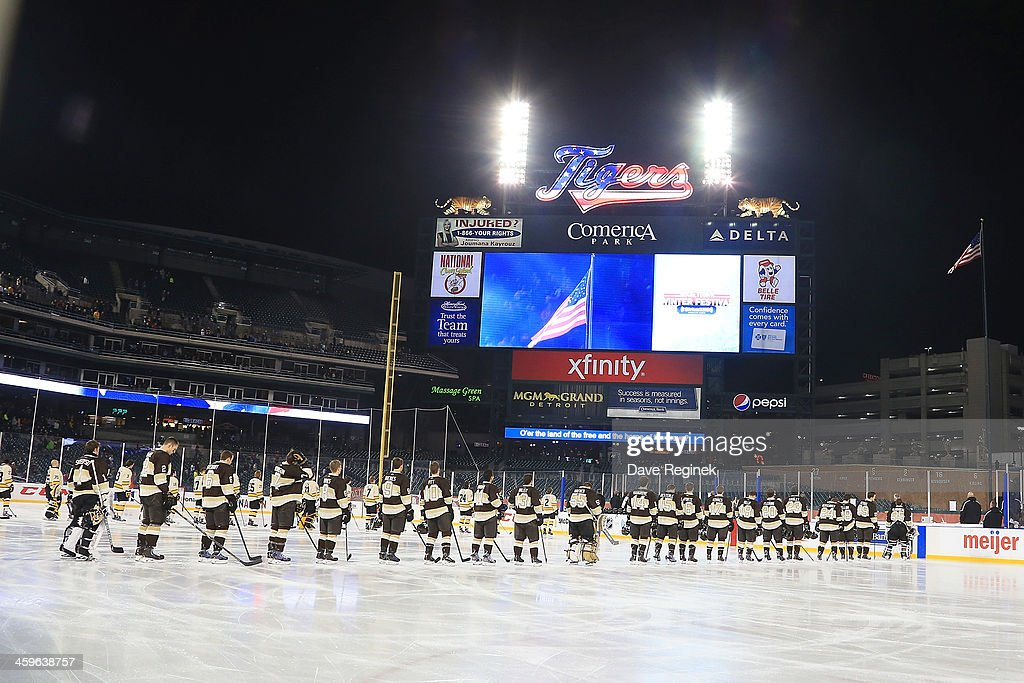Players from the Michigan Tech Huskies and the Western Michigan Broncos stand for the national anthem before the championship game of the Hockeytown Winter Festival Great Lakes Invitational - Day 2 played outdoors at Comerica Park on December 28, 2013 in Detroit, Michigan.