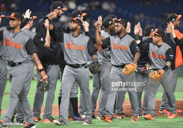 TOPSHOT Players from the Netherlands celebrate their win after the bottom of the seventh inning in the World Baseball Classic Pool E second round...