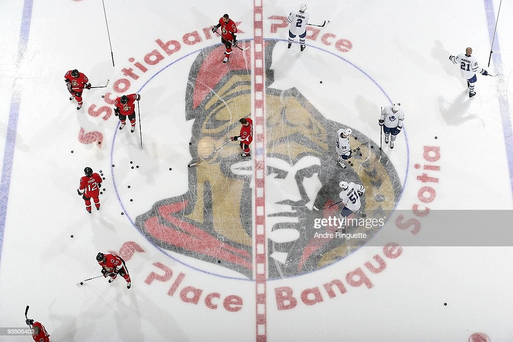 Players from the Ottawa Senators and the Toronto Maple Leafs skate over the centre ice logo during warmup prior to a game at Scotiabank Place on...