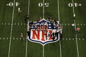 Players from the San Francisco 49ers and the Baltimore Ravens stand on the NFL logo for the opening coin toss during Super Bowl XLVII at the...