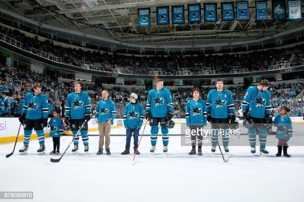 Players from the San Jose Sharks stand with Kaiser Permanente pediatric patients at Hockey Fights Cancer night during the National Anthem prior to a...