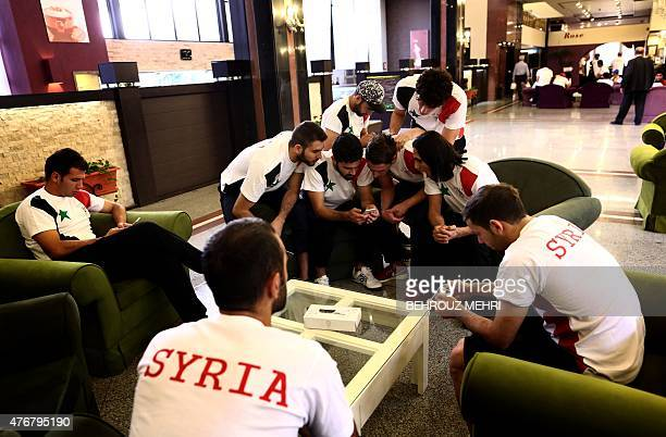 Players from the Syrian national football team check their cell phones in the lobby of a hotel before the 2018 World Cup qualifying group E football...
