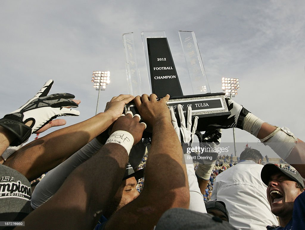Players from the Tulsa Golden Hurricane hold the trophy after the C-USA championship game against the Central Florida Knights on December 1, 2012 at H.A. Chapman Stadium in Tulsa, Oklahoma. Tulsa defeated Central Florida 33-27 in overtime.