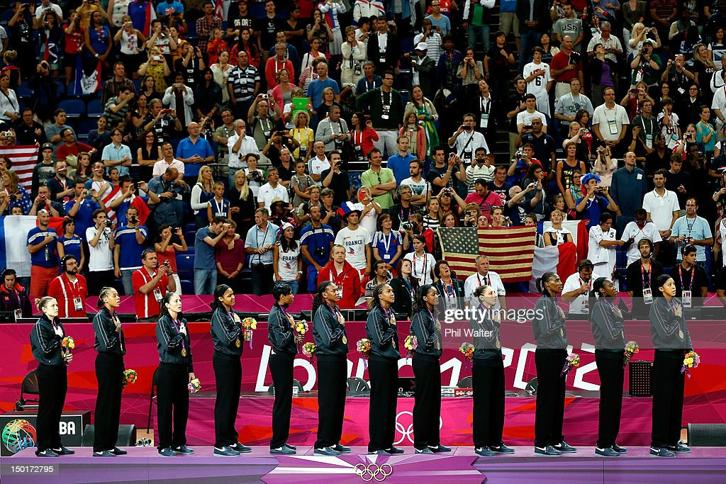 Players from the United States stand on the podium during the playing of the United States national anthem after they received their gold medlas during the medal ceremony for the Women's Basketball on Day 15 of the London 2012 Olympic Games at North Greenwich Arena on August 11, 2012 in London, England.