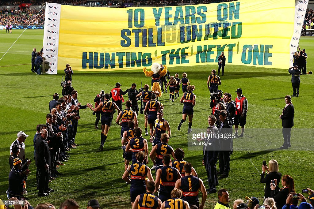 Players from the West Coast Eagles 2006 Premiership Team form a guard of honour as the 2016 team run onto the arena during the round 15 AFL match between the West Coast Eagles and the Essendon Bombers at Domain Stadium on June 30, 2016 in Perth, Australia.