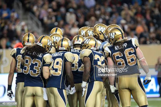 Players from the Winnipeg Blue Bombers discuss their strategy in a CFL game against the Toronto Argonauts at Investors Group Field on June 26 2014 in...