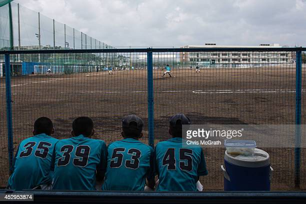 Players from the Yokohama Minami watch on from the dugout during a practice game between the Shonan Boys and the Yokohama Minami on July 30 2014 in...