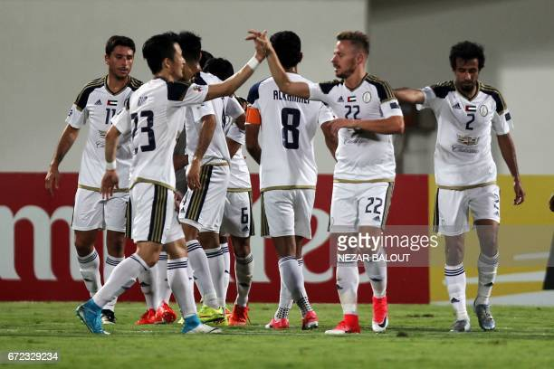 Players from UAE AlWahda FC's celebrate their goal against Qatar's AlRayyan SC during their AFC Champions League group D football match at AlNahyan...