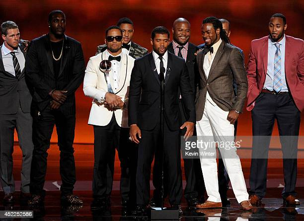 NFL players Golden Tate Malcolm Smith Russell Wilson Richard Sherman and teammates from the Seattle Seahawks accept the Best Team award onstage...