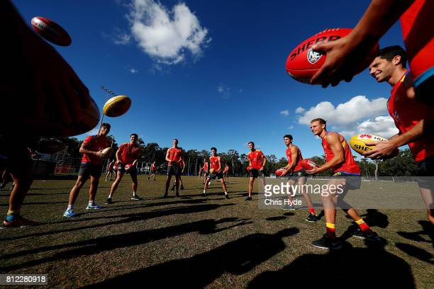 Players handball during a Gold Coast Suns AFL training session at Palm Beach Currumbin AFC on July 11 2017 in Gold Coast Australia
