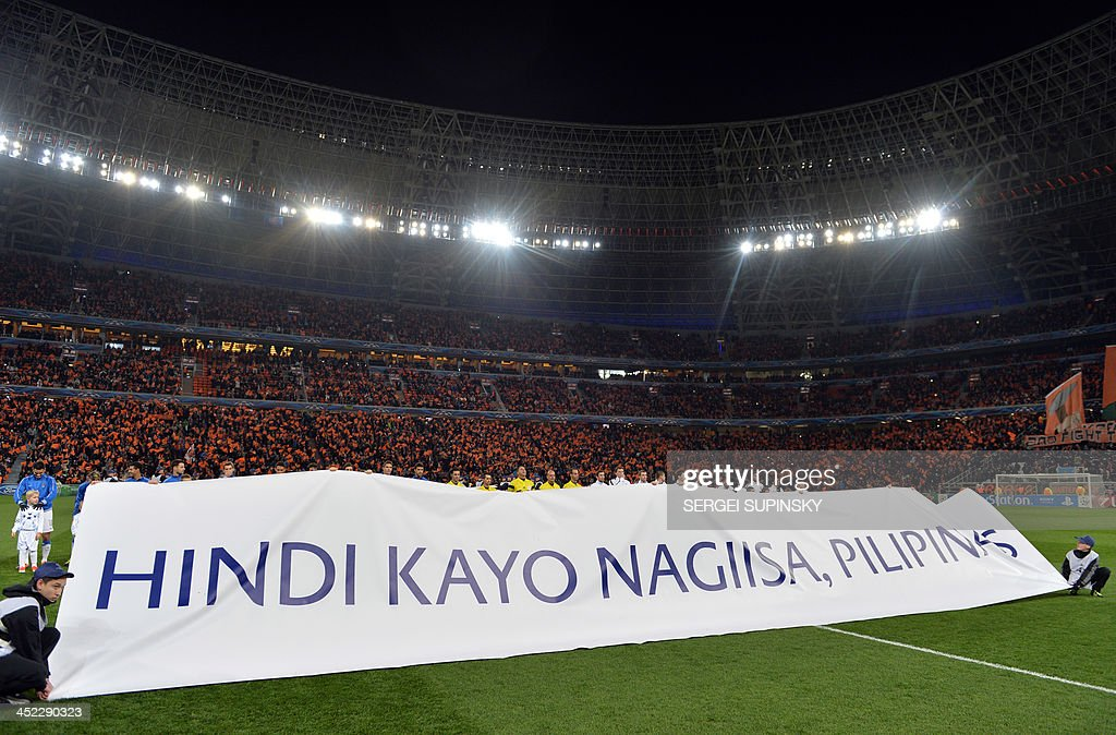 Players hold a banner reading ''You are not alone, Philippines'' to show support to the Philippines, hit by Super Typhoon Haiyan, prior to the UEFA Champions League Group A football match between FC Shakhtar Donetsk and Real Sociedad in Donetsk on November 27, 2013. Super Typhoon Haiyan left almost 7,000 people dead or missing when it swept through the central Philippine islands early this month.