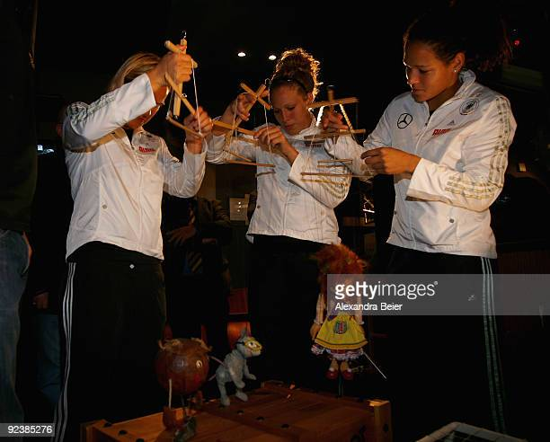 Players Jennifer Zietz Celia Okoyino da Mbabi and Kim Kulig of the women's German national team play with marionettes during their visit at the...