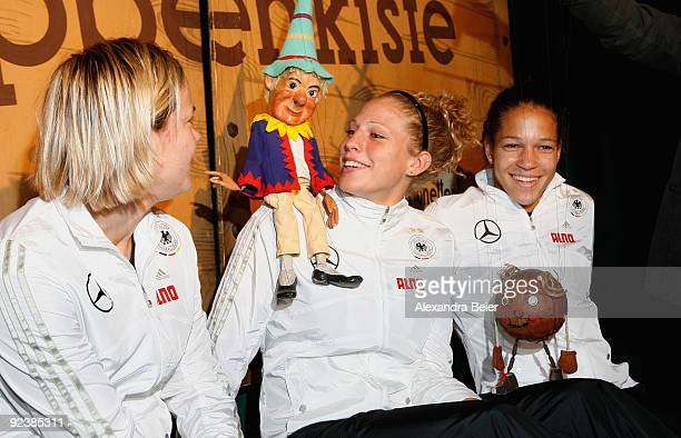 Players Jennifer Zietz Celia Okoyino da Mbabi and Kim Kulig of the women's German national soccer team pose with marionettes during their visit at...