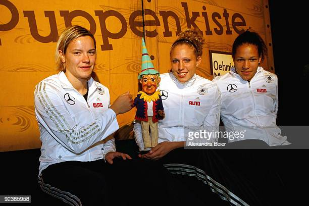 Players Jennifer Zietz Celia Okoyino da Mbabi and Kim Kulig of the women's German national soccer team pose with a marionette during their visit at...