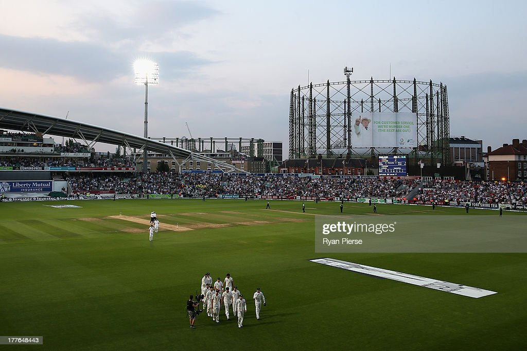 Players leave the field after bad light ended the match during day five of the 5th Investec Ashes Test match between England and Australia at the Kia Oval on August 25, 2013 in London, England.