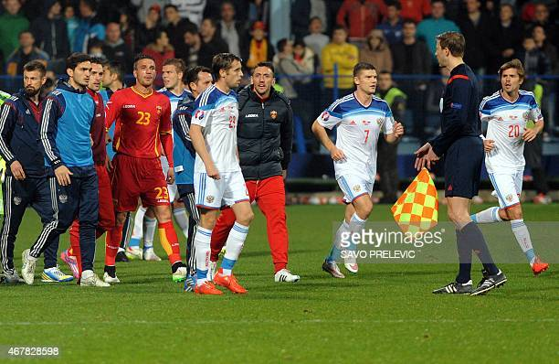 Players leave the pitch as the referee suspends the Euro 2016 group G qualifying football match between Montenegro and Russia at the City stadium in...