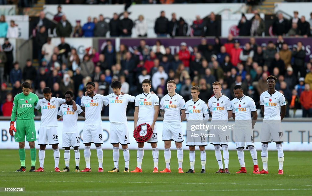 Players line up for a minute's silence ahead of Remembrance Sunday prior to the Premier League match between Swansea City and Brighton and Hove Albion at Liberty Stadium on November 4, 2017 in Swansea, Wales.