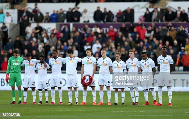Players line up for a minute's silence ahead of Remembrance Sunday prior to the Premier League match between Swansea City and Brighton and Hove...