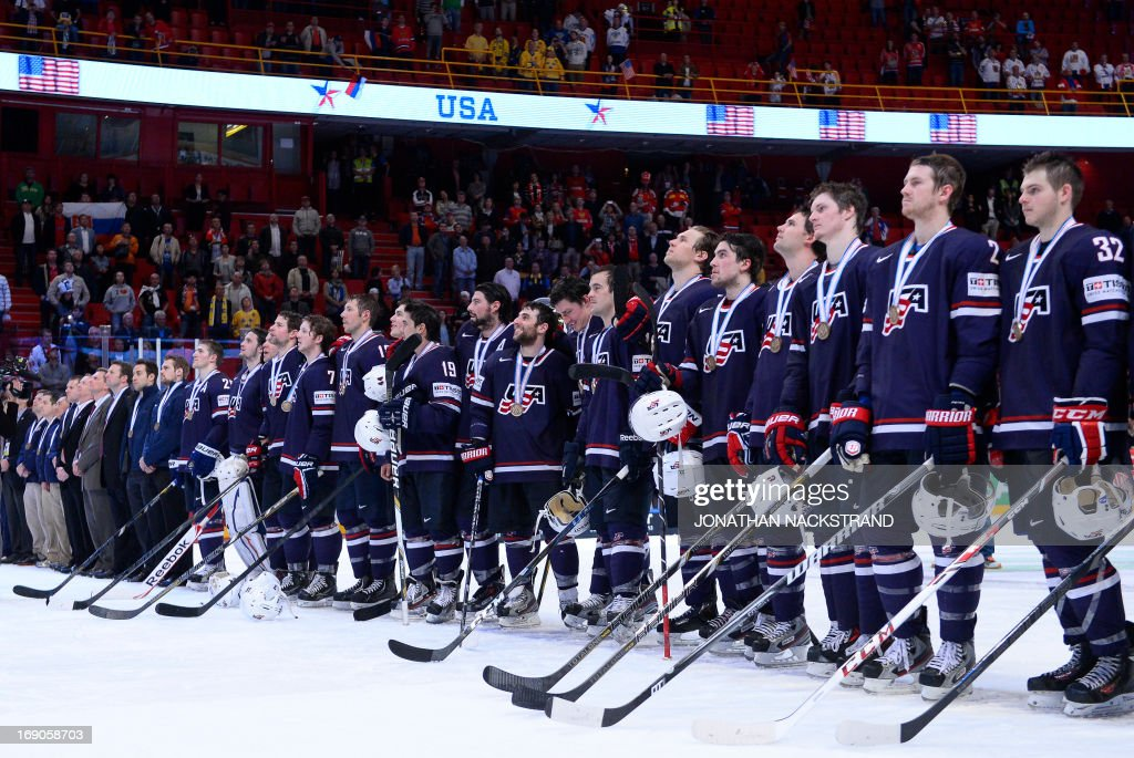 US players listen to their national anthem with their bronze medal after the 2013 IIHF Ice Hockey World Championship bronze medal match Finland vs USA on May 19, 2013 in Stockholm. USA won 3-2.