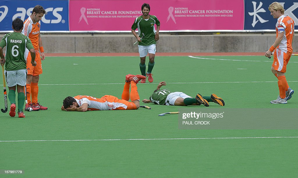 Players look on as Muhammad Rizwan Snr (on pitch R) of Pakistan and Valentin Verga (on pitch L) of the Netherlands lie on the pitch after clashing heads during their semifinal at the men's Hockey Champions Trophy tournament in Melbourne on December 8, 2012. IMAGE STRICTLY RESTRICTED TO EDITORIAL USE - STRICTLY NO COMMERCIAL USE AFP PHOTO / Paul CROCK