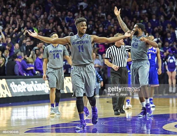 Players Nino Williams and Thomas Gipson of the Kansas State Wildcats celebrate as the Wildcats defeat the Kansas Jayhawks 7063 on February 23 2015 at...