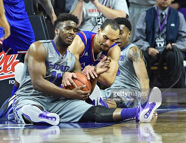 Players Nino Williams of the Kansas State Wildcats and Perry Ellis of the Kansas Jayhawks battle for the ball during the first half on February 23...